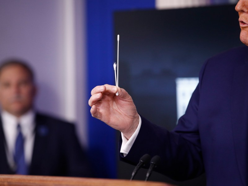 President Donald Trump demonstrates the difference between a COVID test swab and a Q-tip on April 19th. California announced it would receive federal shipments of hundreds of thousands of swabs in the coming weeks. Photo by Patrick Semansky, AP Photo