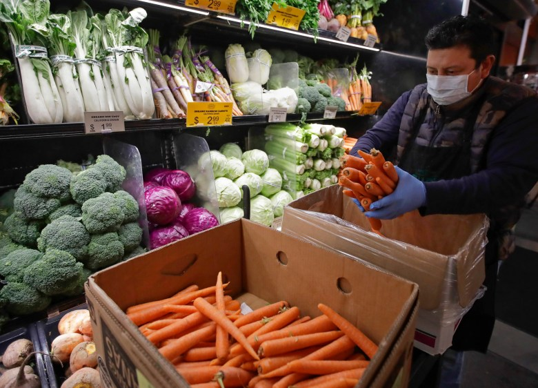 California grocery workers hope the state adopts a new rule making it easier for essential workers like them to receive workers' comp benefits if they contract COVID-19. This masked worker stocks produce at Gus's Community Market in San Francisco. Photo by Ben Margot, AP Photo