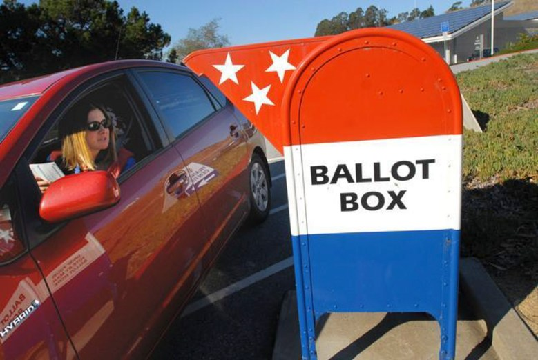 A woman drops off a ballot from her car. Photo by Dan Honda, Bay Area News Group