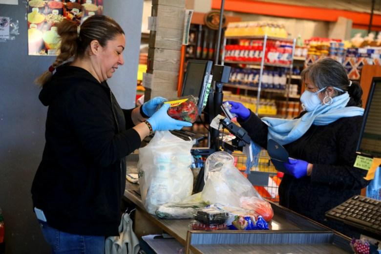 Employee Jadira De Alvarez, left, checks out a customer at Mi Tierra Foods on April 1 in Berkeley, Calif. Photo by Aric Crabb, Bay Area News Group