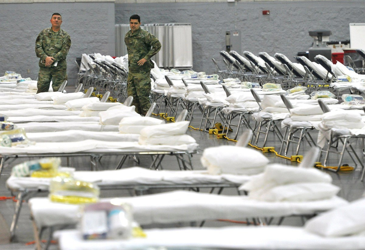 Members of the Air National Guard look over a field hospital set up in the Fresno Convention Center to provide additional hospital beds in response to the coronavirus pandemic. Photo by John Walker, The Fresno Bee