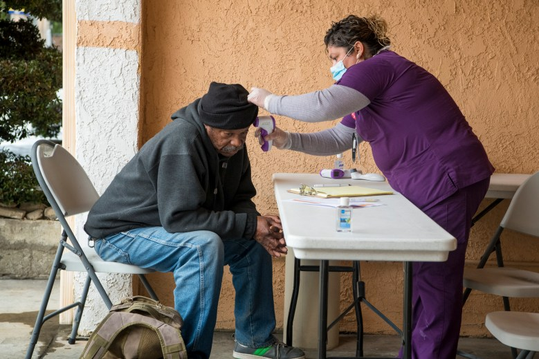 CNA Yesenia Chavez checks the temperature of Grehlin Wright who was registering for a hotel room through Project Roomkey in LA County on April 7, 2020. Photo by Michael Owen Baker courtesy of Los Angeles County
