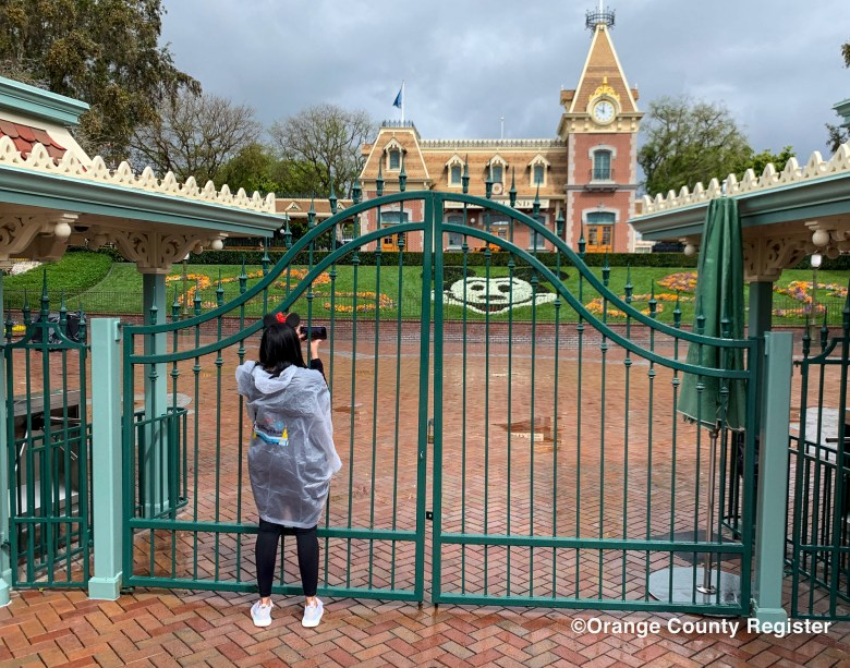 A visitor to the Disneyland Resort takes a picture through a locked gate at the entrance to Disneyland in Anaheim, CA, on Monday, Mar 16, 2020.