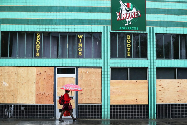 A pedestrian walks past boarded up windows of a business in Oakland on the the eighth day of the shelter-in-place order meant to reduce the spread of coronavirus on March 24, 2020.
