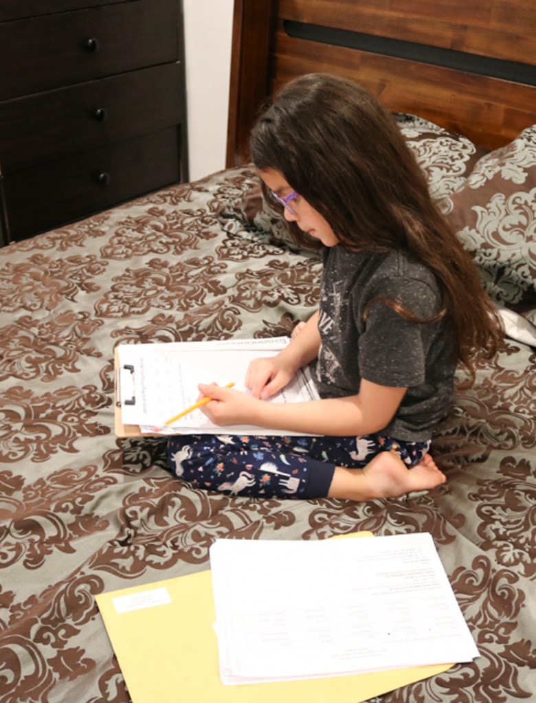 Melina, 8, does homework in her parents' bedroom. Photo courtesy of Raul Torres