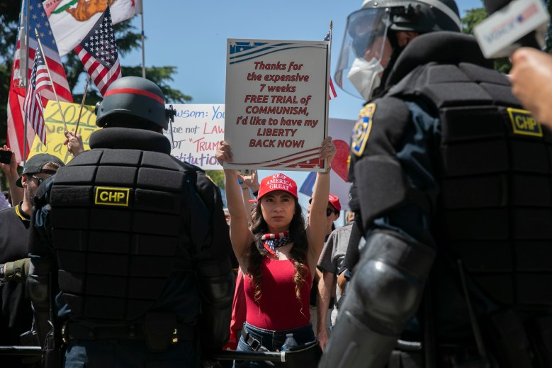 "A woman holds up a sign as California Highway Patrol officers push back against protesters at a Capitol ""Reopen California"" anti-Newsom protest amid the coronavirus pandemic. Many participants did not wear protective masks or follow social distancing guidelines. Photo by Anne Wernikoff for CalMatters"