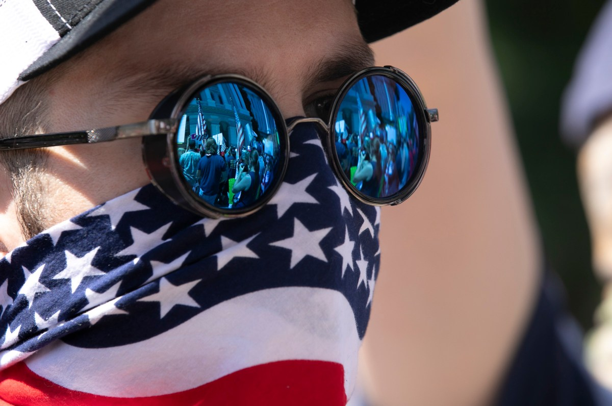 Protesters carrying American flags and signs in front of the California Capitol are reflected in a fellow-protester's sunglasses. Photo by Anne Wernikoff for CalMatters