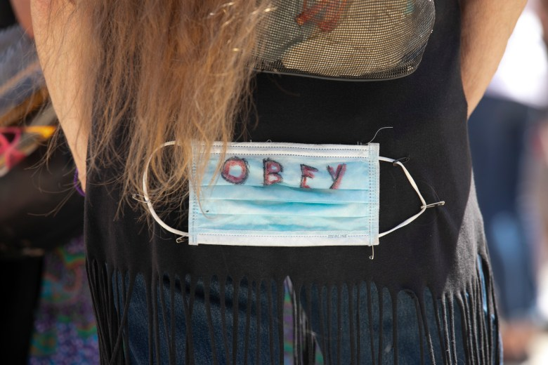 A woman wears a surgical mask with 'Obey' written in marker safety pinned to the back of her top during a protest at the California Capitol demanding that Gov. Gavin Newsom end the shelter in place order. Photo by Anne Wernikoff for CalMatters