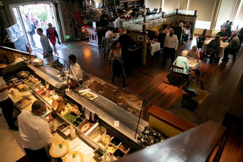 Masked employees work in the open kitchen overlooking the dining room at Cole's Chop House where guests are seated in the dining room reconfigured to meet state requirements for social distancing May 22 in Downtown Napa. Photo by Anne Wernikoff for CalMatters