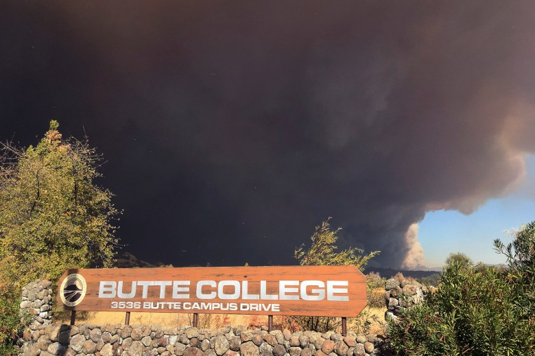 Smoke from the Camp Fire, burning in the Feather River Canyon near Paradise, Calif., darkens the sky above the Butte College sig in Oroville, Calif., Thursday, Nov. 8, 2018. (AP Photo/Don Thompson)