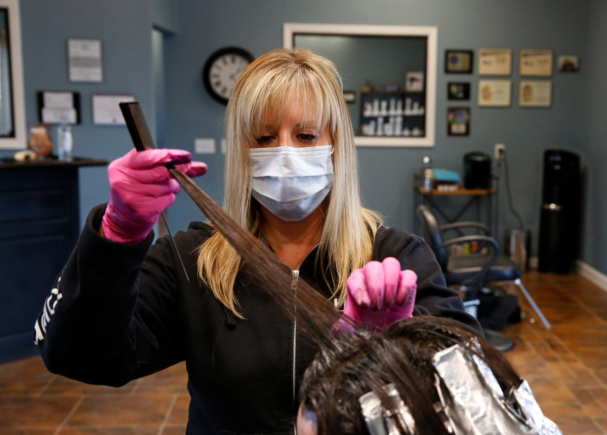 Tisha Fernhoff separates the hair of a client receiving a color refreshing at the Beauty Bar Salon in Auburn on April 29, 2020. Fernhoff closed her shop in March because of the mandatory stay-at-home order but began taking occasional clients in order pay her rent and meet other expenses. Photo by Rich Pedroncelli, AP Photo