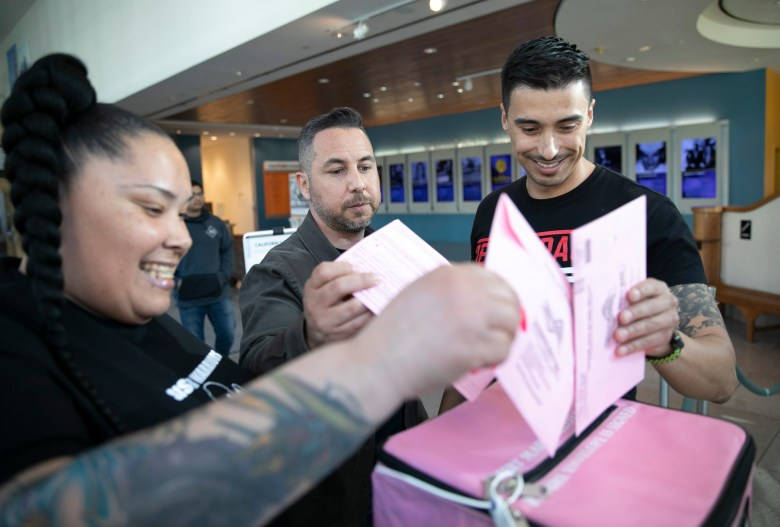 From left: April Greyson, Michael Mendoza and Esteban Nunez submit their presidential primary election ballots at the California Museum in Sacramento on March 2, 2020. Photo by Anne Wernikoff for CalMatters