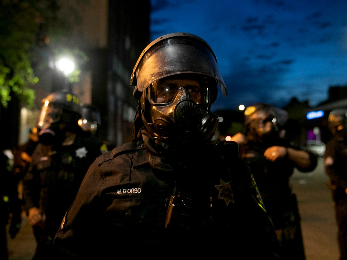 A police offer watches the crowd from behind a gas mask during a demonstration May 29, 2020 Downtown Oakland. Thousands took to the streets Friday night in solidarity with protesters in Minneapolis against the killing of George Floyd by Minneapolis police earlier this week. Photo by Anne Wernikoff for CalMatters