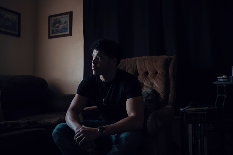 Joshua Dixon sits in the living room where he found his older sister, Breanna Dixon, after she overdosed. Photo by Adam Perez for CalMatters