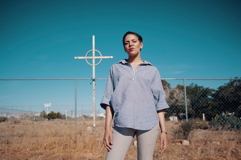 Breanna Dixon stands against a blue sky with a cross in the background.