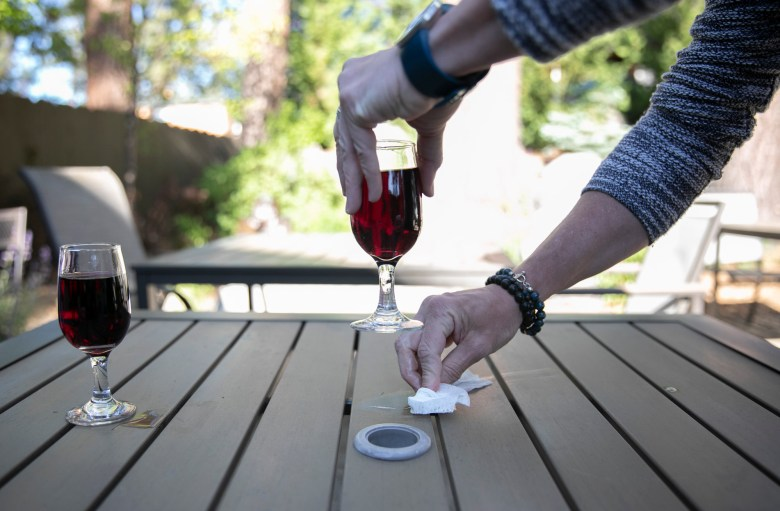 A guest cleans the table with a Clorox wipe during the evening meet and greet at 7 Seas Inn in South Lake Tahoe. Photo by Anne Wernikoff for CalMatters