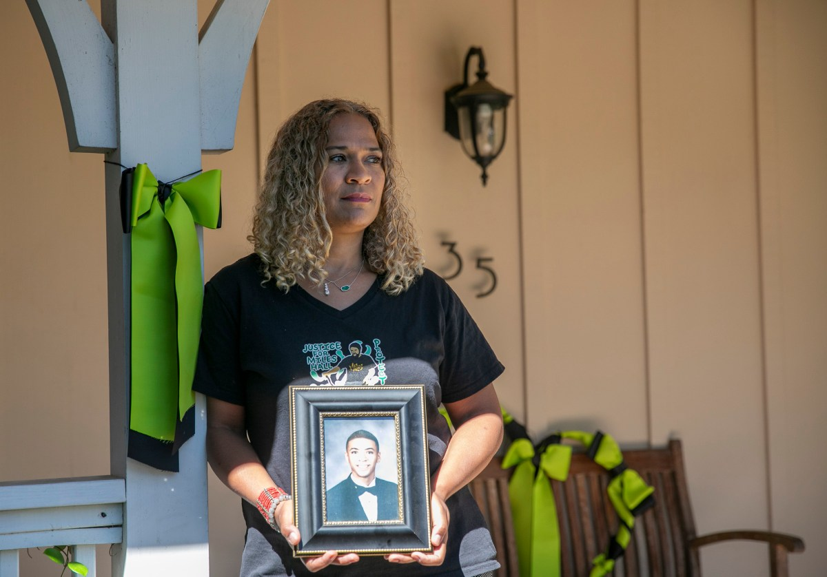 Taun Hall stands on the porch of her Walnut Creek home next to a green ribbon, the international symbol for mental health awareness. She and some of her neighbors display the ribbons in remembrance of her son, Miles, who was killed last year by Walnut Creek police during a mental health crisis. Photo by Anne Wernikoff for CalMatters