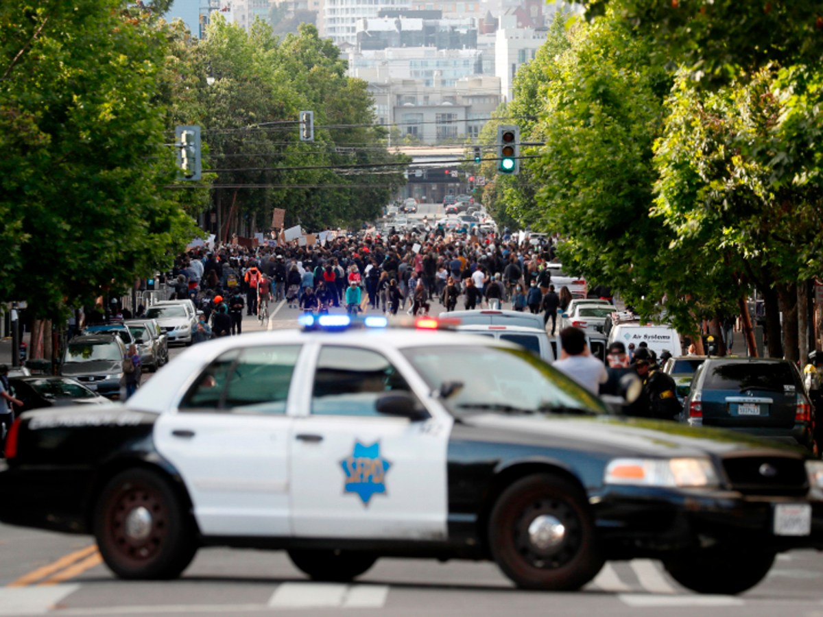 A patrol car closes off Valencia Street in San Francisco after a group of protesters gathered in front of the Mission Police Station on May 30, 2020, the second day of Bay Area unrest over the George Floyd killing in Minneapolis. Later in the year, lawmakers approved two new laws that aim to improve policing. Photo by Karl Mondon, Bay Area News Group