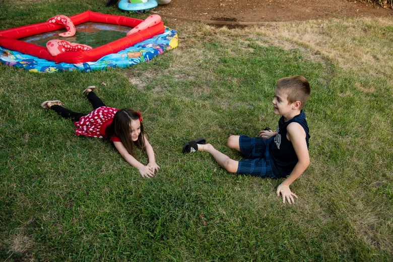 Kyla Hill, 5, left, and Kaden Hill, 7, right, play in their backyard at their home in Chico on July 23, 2020. Photo by Salgu Wissmath for CalMatters