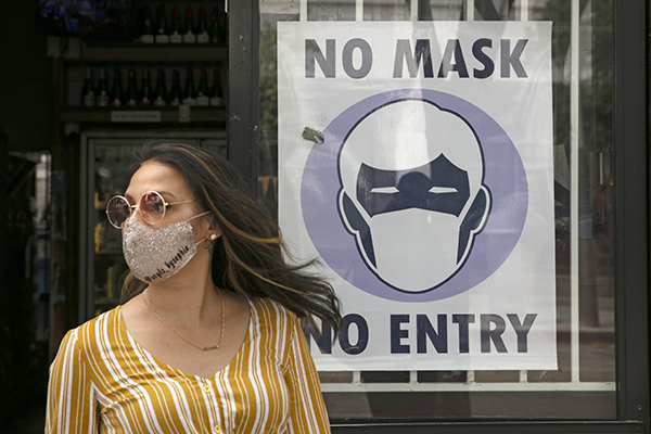 A woman walks out of a liquor store past a sign requesting its customers to wear a mask Tuesday, June 23, 2020, in Santa Monica. California is among the states seeing the greatest surge in cases now. Photo by Jae C. Hong, AP Photo