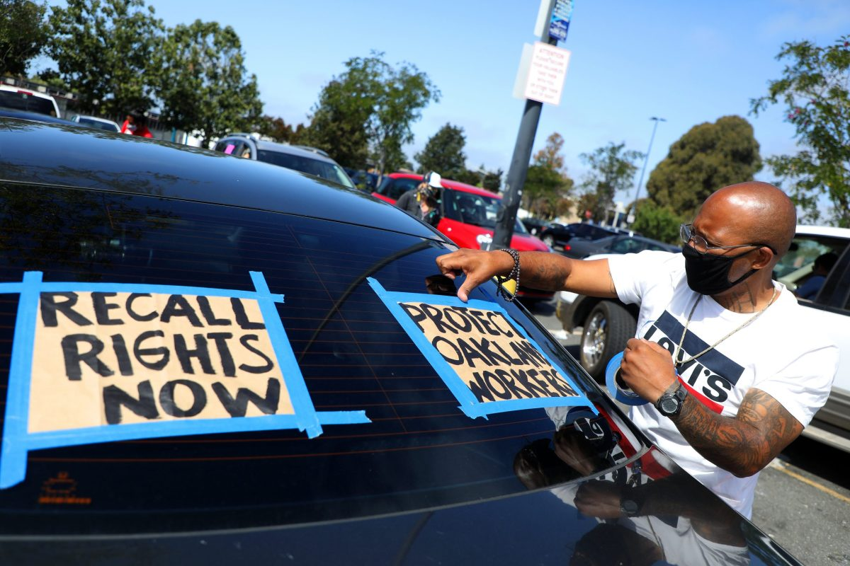 "Saabir Lockett tapes signs to the rear window of a vehicle before the start of a car rally on Monday, July 13, 2020, in Oakland, Calif. The rally was held to support the passage of a city ordinance that would give workers who were laid off during the pandemic a ""right to return"" if companies start to hire again. (Aric Crabb/Bay Area News Group)"