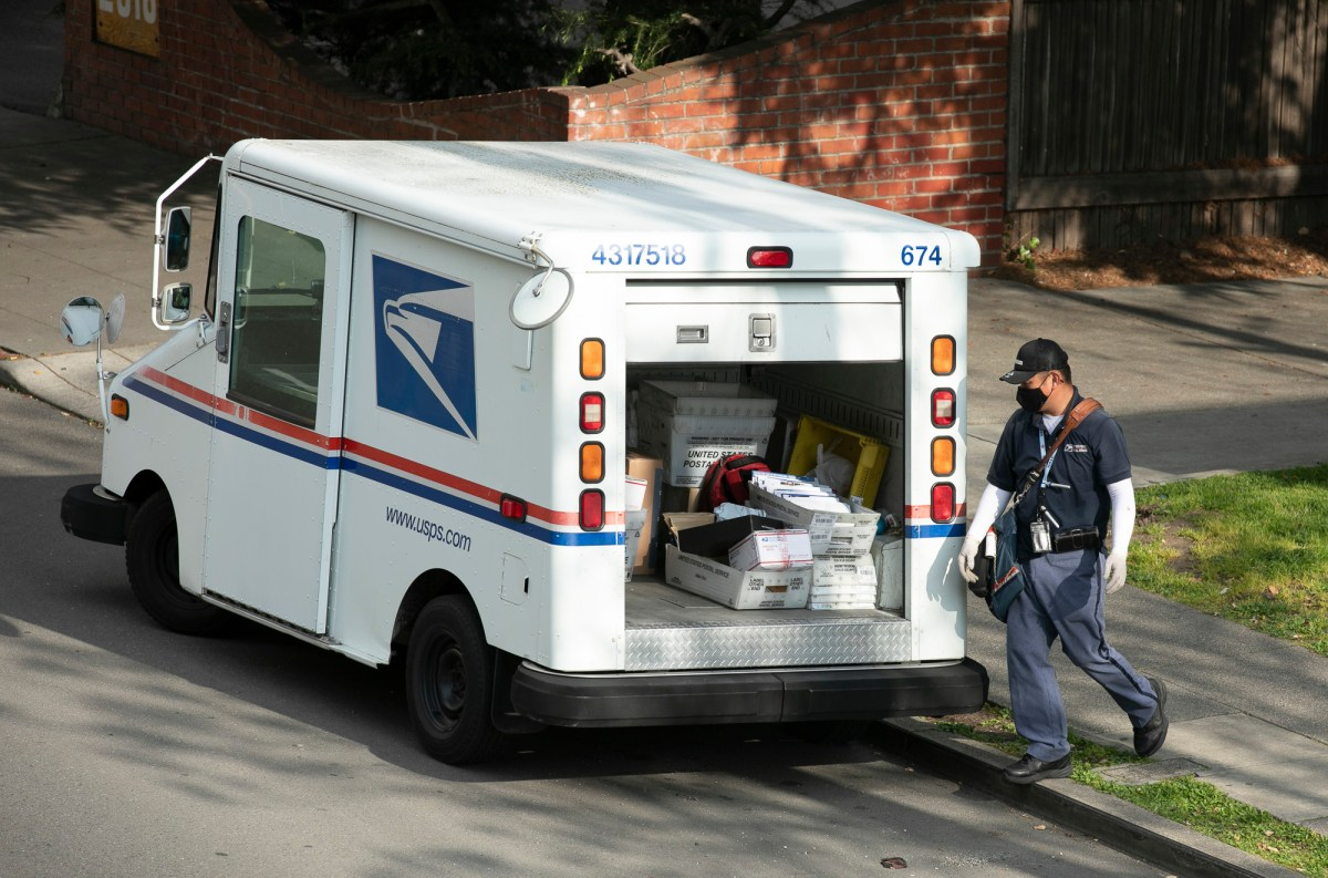 A mail carrier wearing a mask and gloves in Berkeley on March 27, 2020. Postal employees are considered essential during the shelter in place. Photo by Anne Wernikoff for CalMatters