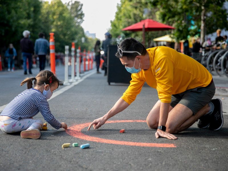 Adam Sciambi, right, and daughter Noa, 3, play with sidewalk chalk on Valencia Street in the Mission neighborhood of San Francisco on July 25, 2020. Several blocks of the neighborhood are closed to vehicles every Thursday through Sunday to allow for outdoor dining and foot traffic. Photo by Anne Wernikoff for CalMatters