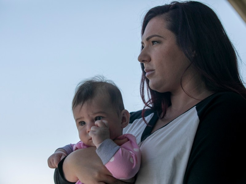 Jessica Gallup and her five-and-a-half-month-old daughter Sunny on the balcony of their one bedroom apartment in South San Francisco on August 6, 2020. Gallup, an event coordinator who cannot work due to the coronavirus pandemic, placed thousands of calls to unemployment agencies before receiving benefits. Now that she will lose the $600 in additional stimulus aid, gallup worries how she will make ends meet. Photo by Anne Wernikoff for CalMatters