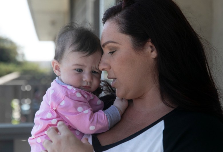 Jessica Gallup and her five-and-a-half-month-old daughter Sunny on the balcony of their one bedroom apartment in South San Francisco on August 6, 2020. Now that she will lose the $600 in additional stimulus aid, Gallup worries how she will make ends meet. Photo by Anne Wernikoff for CalMatters