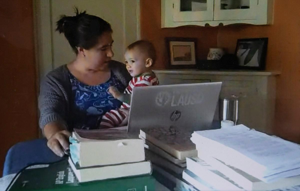 Maya Suzuki Daniels se sienta con su hijo de 14 meses en la mesa donde enseña inglés en la escuela secundaria. Ella espera que su bebé aparezca con frecuencia durante sus clases de Zoom. Fotografía de Anne Wernikoff para CalMatters vía Google Hangout