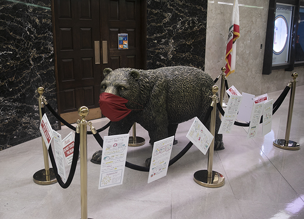 The beat statue outside the governor's office sports a mask and is surrounded by signs encouraging social distancing during the last week of the legislative session on Aug. 28, 2020. Photo by Anne Wernikoff for CalMatters