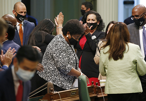 Assemblymember Shirley Weber, center, receives applause from fellow lawmakers during a floor session on June 10, 2020. Weber's bill, AB 1460, was signed into law yesterday making ethnic studies courses a requirement at CSU. Photo by Rich Pedroncelli, AP Photo