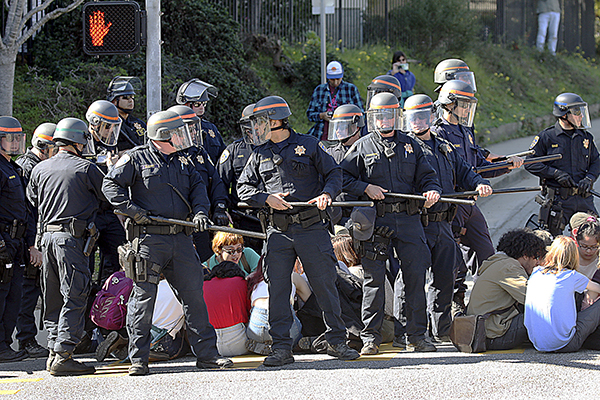 University of California police on Wednesday form a barrier around a group of students before they are arrested and carted away for blocking an intersection at the entrance to UC Santa Cruz. Photo by Dan Coyro, Santa Cruz Sentinel
