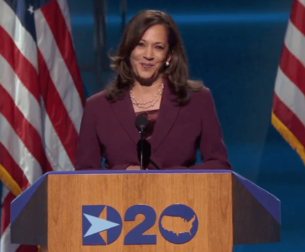 Kamala Harris stands at DNC podium, smiling