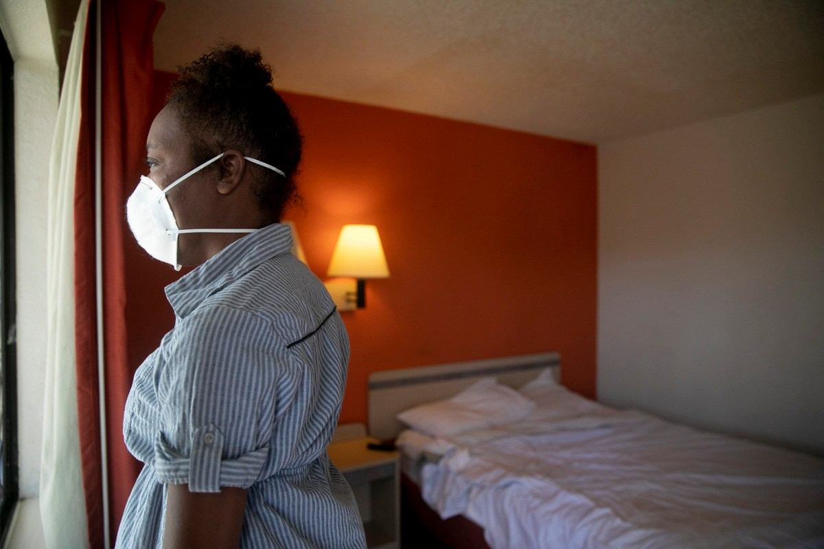 Jamie Burson looks out the window of her motel room in Farfield on August 4, 2020. Burson has been living between her car and motels since being evicted in April. Photo by Anne Wernikoff for CalMatters