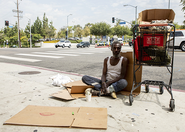 Will, who provided his first name only, sits on the sidewalk across the street from LAC+USC Medical Center on Aug. 7, 2019. Will says he has been homeless since he arrived in Los Angeles from Chicago in 1982. Photo by Anne Wernikoff for CalMatters