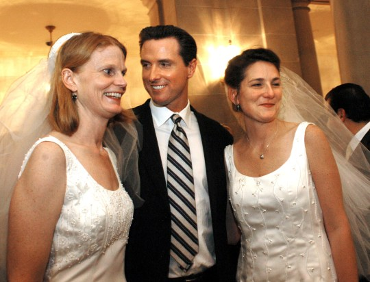 San Francisco Mayor Gavin Newsom stands between newlyweds, Cissie Bonini, left, and Lora Pertle, during a reception at San Francisco City Hall on Feb. 13, 2004. The California Supreme Court ruled unanimously that Newsom overstepped his authority by issuing same-sex marriage licenses later that year. Photo by Erin Lubin, AP Photo