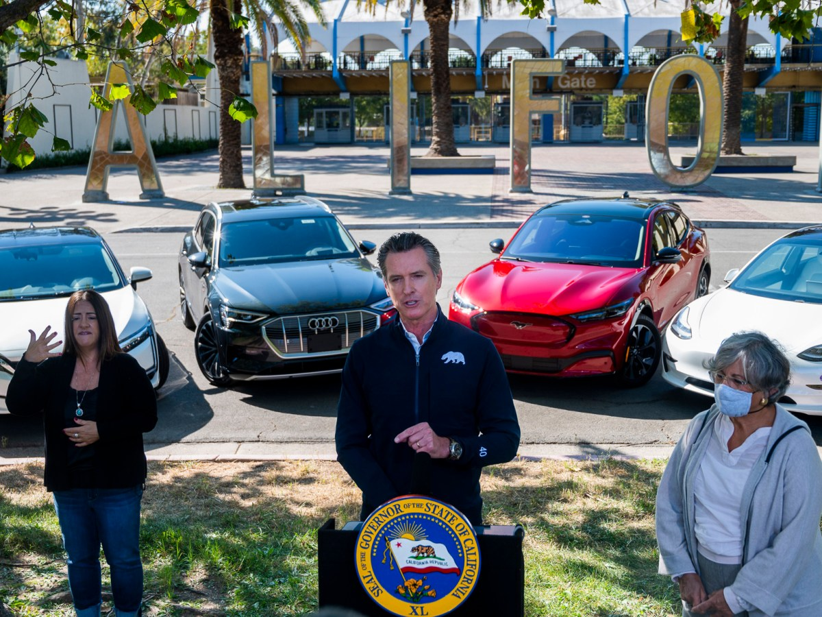 California Gov. Gavin Newsom stands in front of four electric cars to announce an executive order requiring all new passenger vehicles sold in the state to be zero-emission by 2035, a move the governor says would achieve a significant reduction in greenhouse gas emissions, on Sept. 23, 2020, at Cal Expo in Sacramento. Photo by Daniel Kim, The Sacramento Bee via AP/Pool