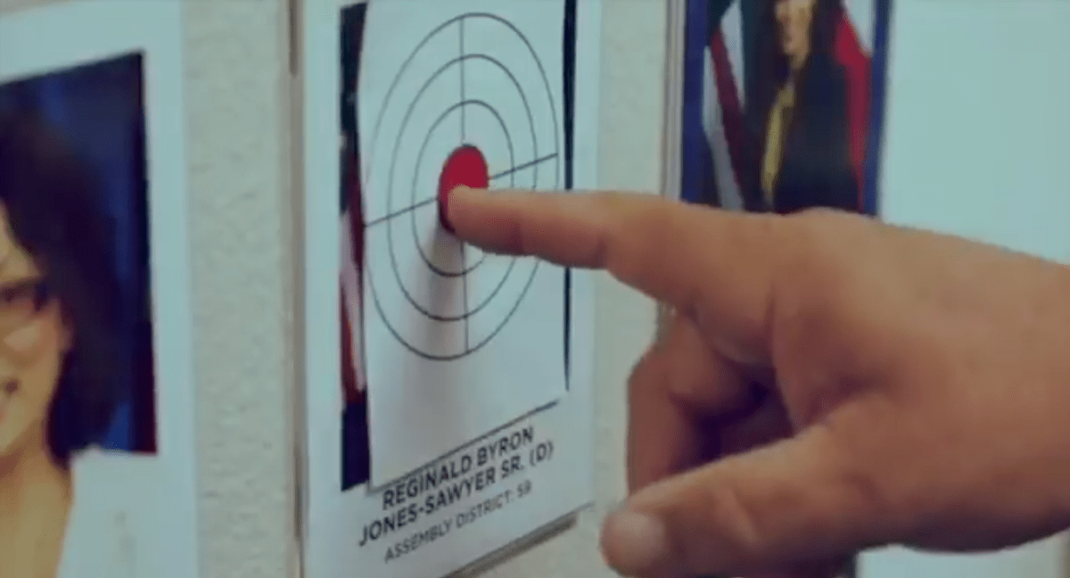 A finger points at a bullseye taped over the official portrait of Democratic Assemblyman Reggie Jones-Sawyer
