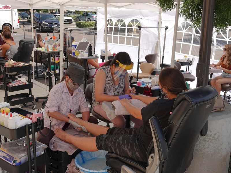 In order to comply with local regulations, a Vista, Ca nail salon operates outside on Aug. 1, 2020. Photo by Simone Hogan via iStock