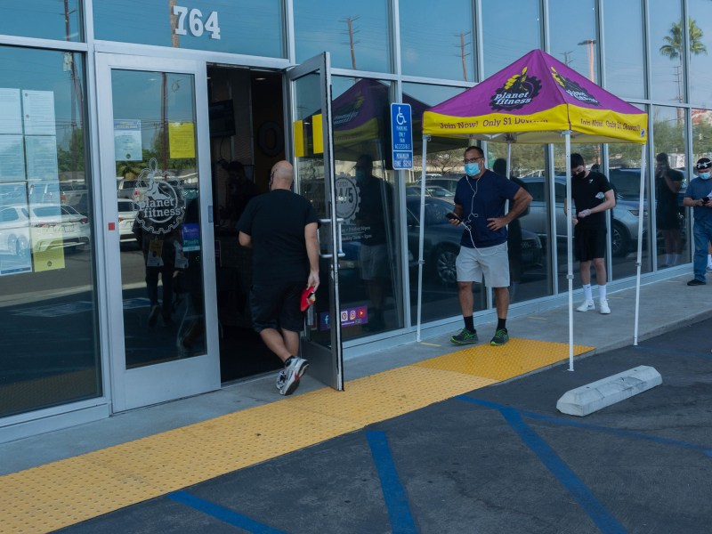 People wait in line at a Planet Fitness in Orange, CA. The gym is now functioning at about 15 percent capacity following the re-opening of a handful of franchises in Los Angeles and Orange County. Oct 8, 2020. Photo by Tash Kimmell for CalMatters.