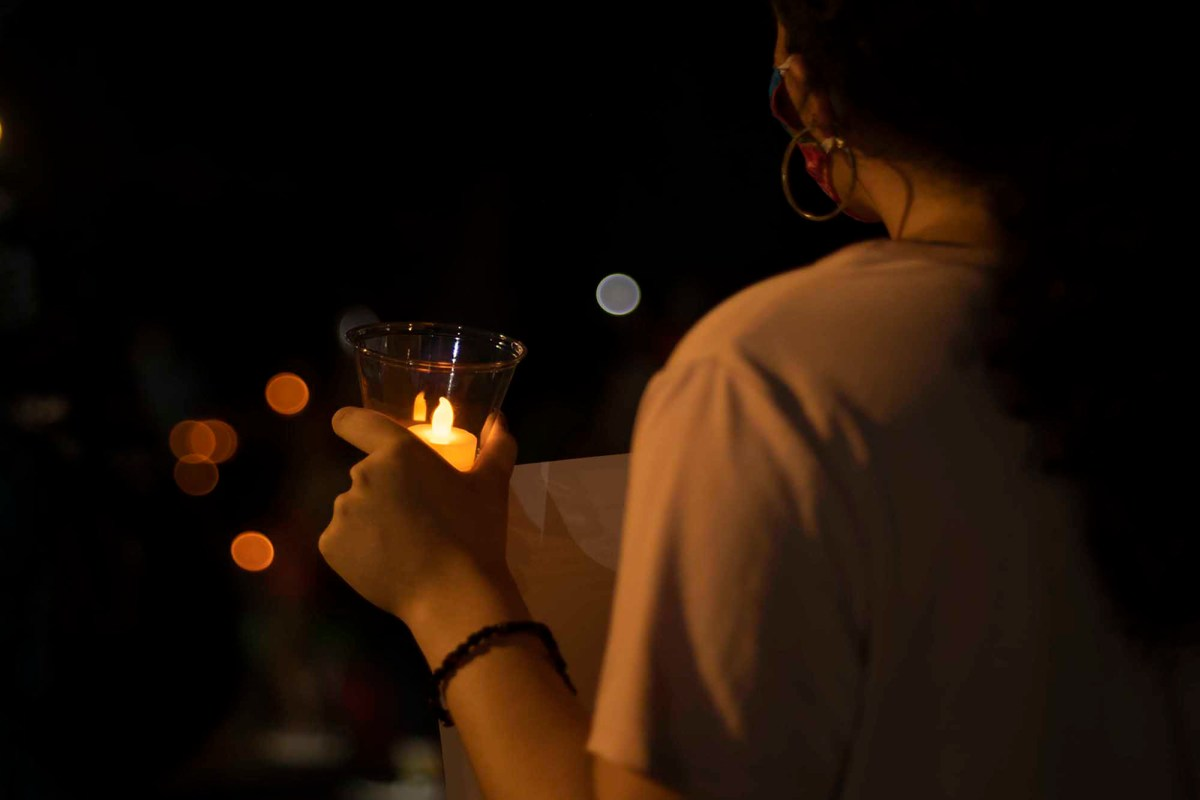 A protestor holds a candle in solidarity with the 19,000 plus recorded Amazon workers infected with Covid-19 since the start of the pandemic. Photo by Tash Kimmell for CalMatters.