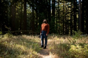 Saxon Stahl, a fourth year student at UC Santa Cruz, stands in the woods across from their residence hall on Oct. 14, 2020. The heavily wooded campus had a mandatory evacuation for more than a week during the CZN Lightening Complex fires in August. Photo by Anne Wernikoff for CalMatters