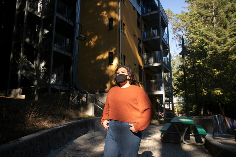 Saxon Stahl, a fourth year student at UC Santa Cruz, stands outside of the laundry building near their residence hall on Oct. 14, 2020. Stahl, who had voluntarily evacuated campus, returned to their dorm to do some laundry when the mandatory evacuation order was announced. Photo by Anne Wernikoff for CalMatters