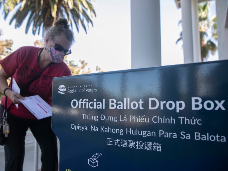 A voter drops off her ballot at Emeryville City Hall on Oct. 15, 2020. Photo by Anne Wernikoff for CalMatters