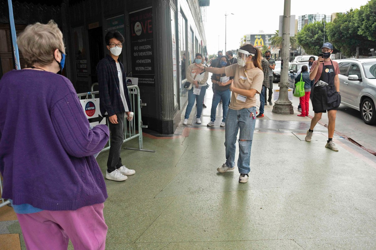 A poll working ushers a voter into the Wiltern Theater in Los Angeles' Korea Town neighborhood on Oct. 24, 2020. Photo by Tash Kimmell for CalMatters.