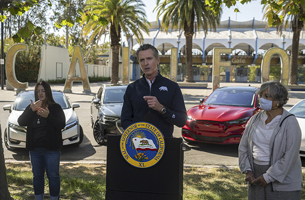 Gov. Gavin Newsom stands in front of four electric cars to announce an executive order requiring all new passenger vehicles sold in the state to be zero-emission by 2035 on Sept. 23, 2020, at Cal Expo in Sacramento. Photo by Daniel Kim, The Sacramento Bee via AP/Pool