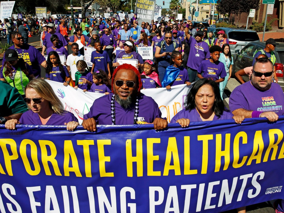 Kaiser Oakland Medical Center employees lead a march down West Macarthur Boulevard as part of a statewide Labor Day protest organized by Service Employees International Union-United Healthcare Workers West on Sept. 2, 2019. Photo by Dylan Bouscher, Bay Area News Group