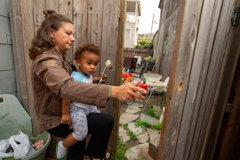 Christine Hernandez carries her son Malikaih Grasso, 1 1/2, as she opens the door of the backyard of their home in Oakland, on Thursday, Oct. 1, 2020. Hernandez with her family of four moved into the apartment building without signing a lease two years ago. With the help of the Bay Area Community Land Trust, they bought the property. Now she is on her way to becoming a radical real estate lawyer. Photo by Ray Chavez, Bay Area News Group