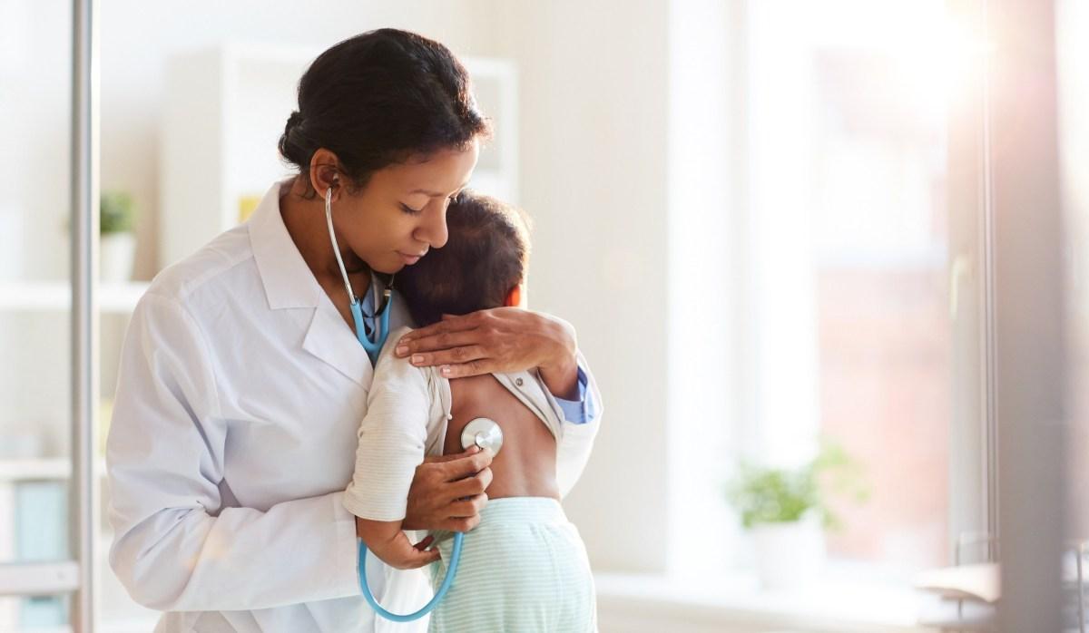 Una médica con chaqueta blanca usando un estetoscopio y escuchando el corazón de su pequeño paciente en el hospital